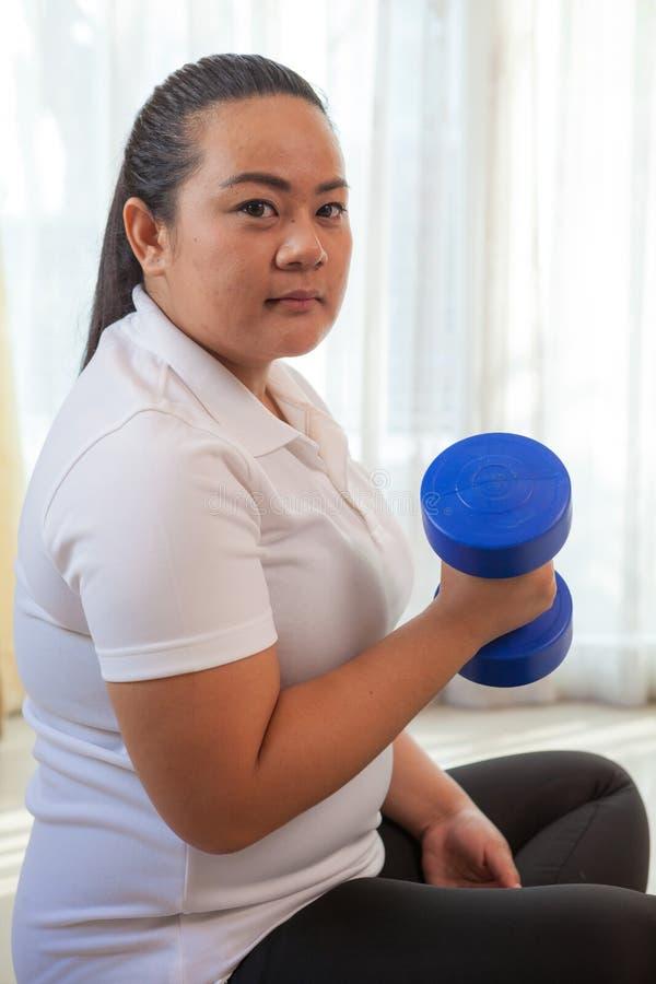 La jeune grosse femme asiatique fait la forme physique avec l'haltère photographie stock