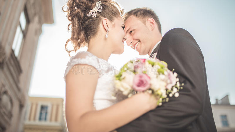 La jeune jeune mariée heureuse de couples de mariage rencontre le marié un jour du mariage Nouveaux mariés heureux sur la terrass photo libre de droits