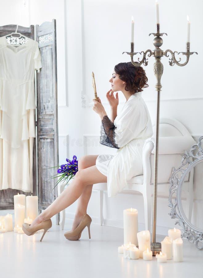 La jeune jeune mariée regarde dans le miroir Matin nuptiale images libres de droits