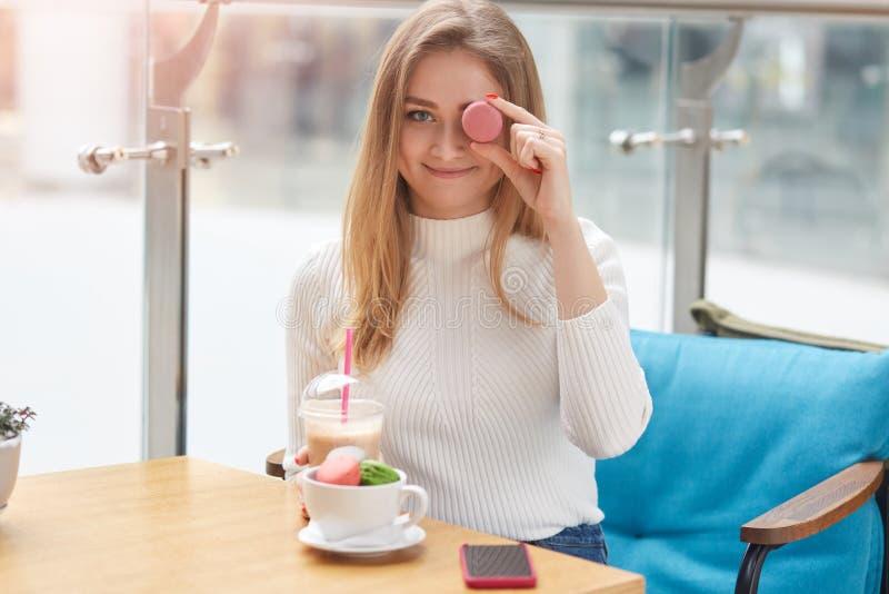 La jeune jolie dame dans la chemise blanche s'assied à la table sur le sofa bleu et couvre son oeil de macaron rose tout en joyeu photo libre de droits