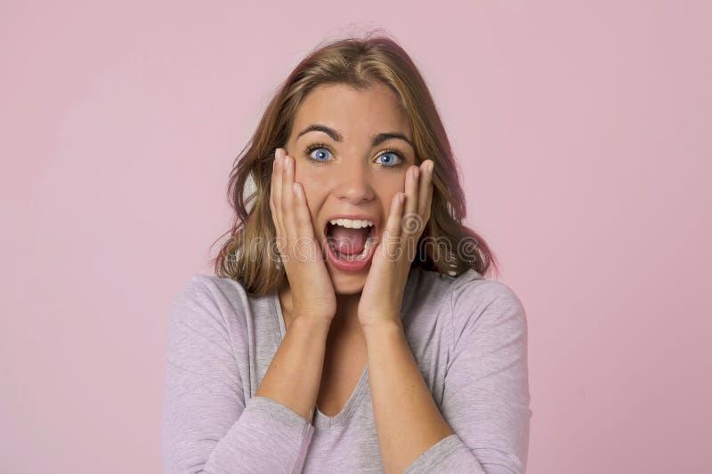 La jeune jolie et attirante fille caucasienne blonde avec de beaux yeux bleus sur son 20s excité et heureux avec la bouche s'est  photographie stock