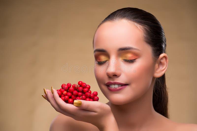 La jeune jolie femme avec des baies dans le concept de beauté image libre de droits