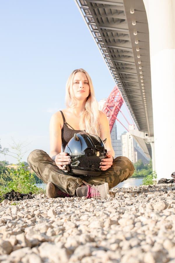 La jeune jolie femme avec le casque pour la moto s'assied au sol images stock