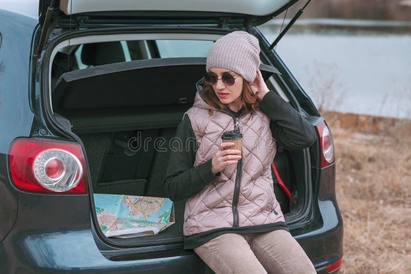 La jeune jolie femme avec la tasse de caf? s'assied dans le tronc ouvert de la voiture pr?s de la rivi?re et de la carte de route image libre de droits