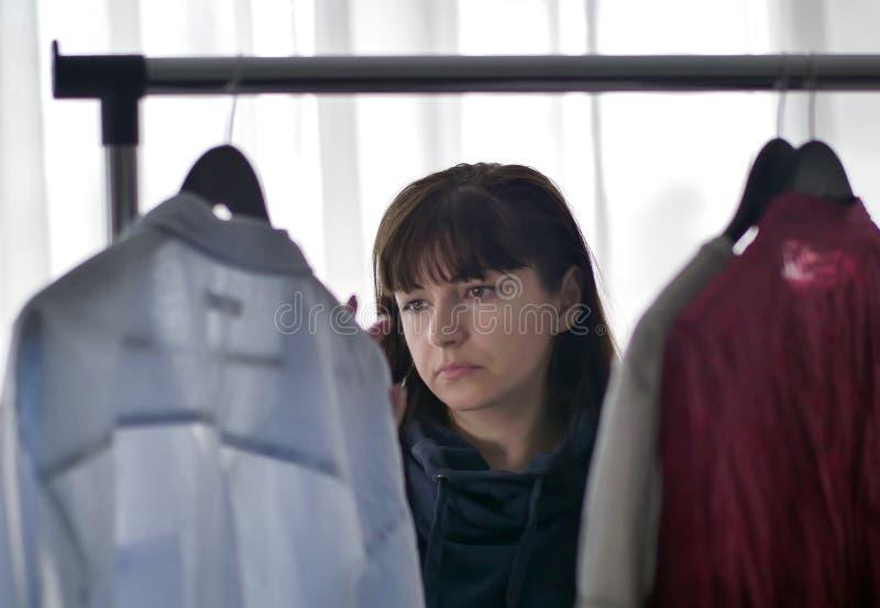 La jeune jolie femme de brune choisit des vêtements des cintres images stock