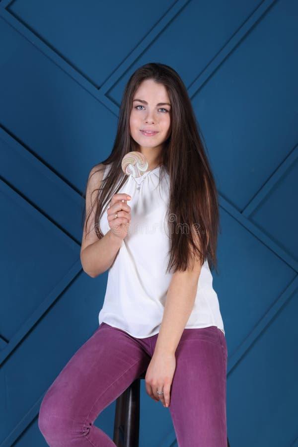 La jeune jolie femme pose sur des selles avec la lucette images stock