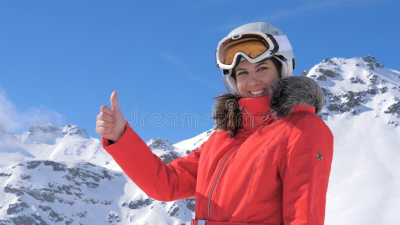 La jeune jolie femme sourit et donne des pouces vers le haut d'un fond de montagne de Milou photos stock