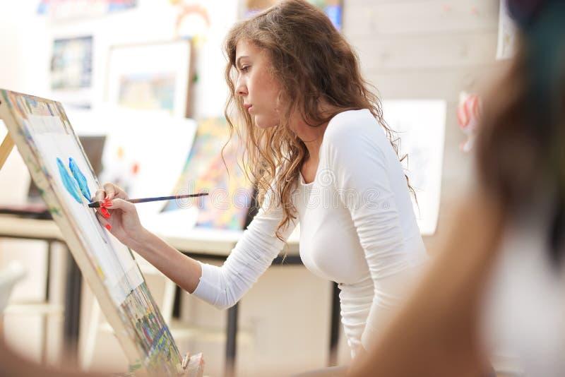 La jeune jolie fille avec les cheveux boucl?s bruns habill?s dans le chemisier blanc peint un tableau au chevalet dans l'?cole de image stock