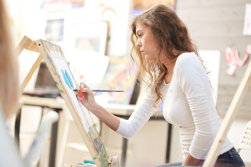 La jeune jolie fille avec les cheveux boucl?s bruns habill?s dans le chemisier blanc peint un tableau au chevalet dans l'?cole de image libre de droits