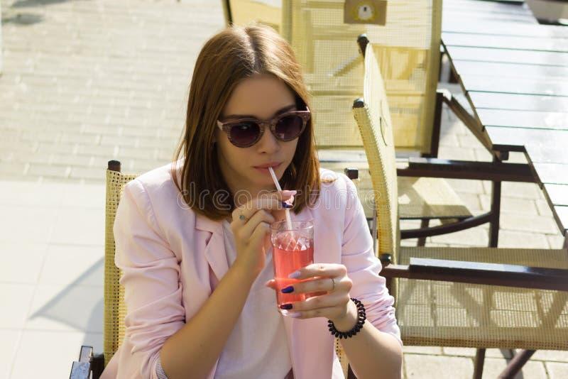La jeune jolie fille boit une boisson froide, extérieure images stock