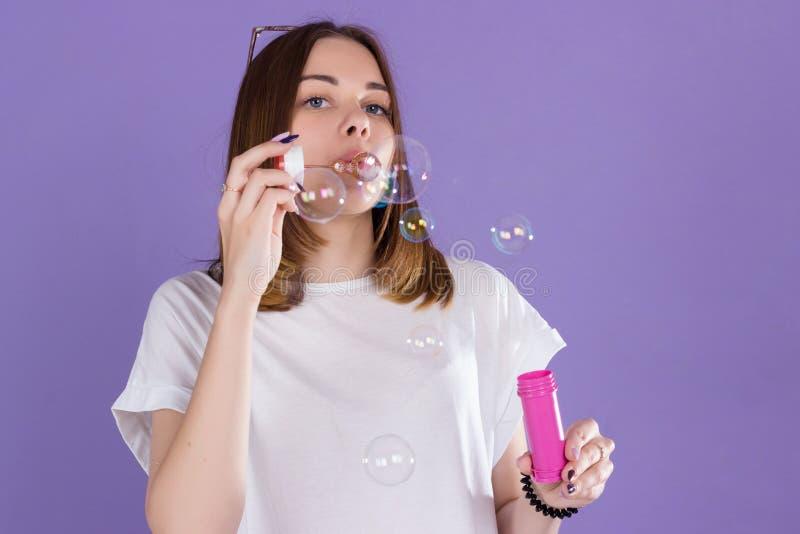 La jeune jolie fille souffle des bulles de savon, studio photographie stock libre de droits