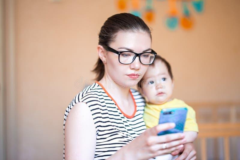 La jeune mère avec peu de bébé sur des mains tient le téléphone intelligent et le regard sur l'écran, utilise des appareils élect image libre de droits