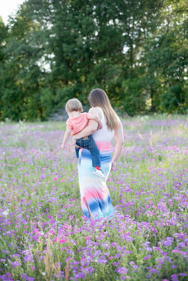 La jeune mère avec son bébé dans des ses bras marche dans le domaine de fleur photographie stock