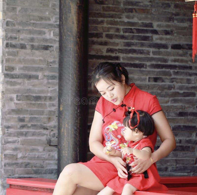 la jeune mère chinoise de famille heureuse a l'amusement avec le bébé dans le cheongsam traditionnel de la Chine image libre de droits