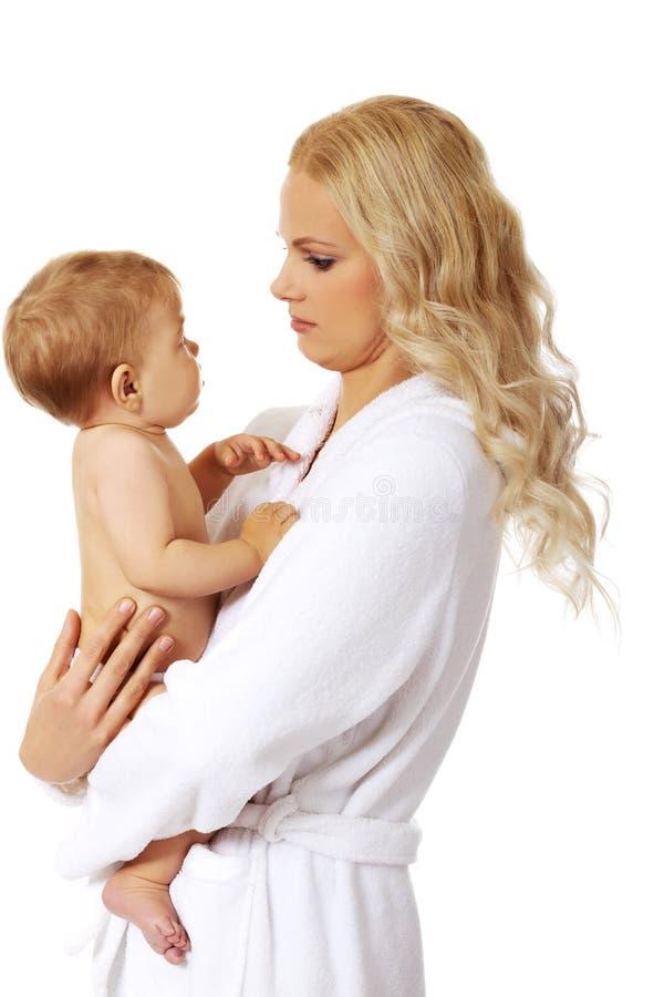 La jeune mère de sourire dans le peignoir tient son bébé photographie stock libre de droits