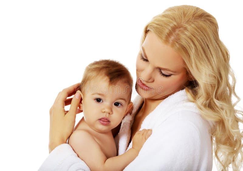 La jeune mère de sourire dans le peignoir tient son bébé photos stock