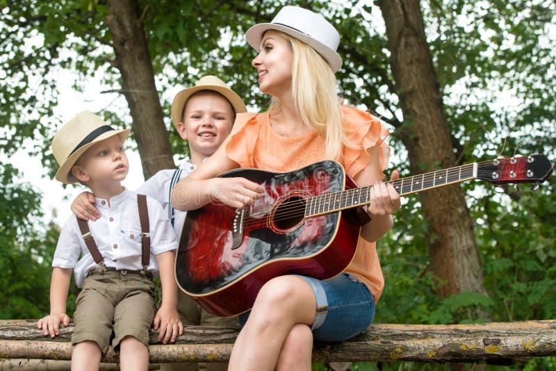 La jeune mère et deux fils se reposent dans les bois, chantant des chansons avec une guitare image libre de droits
