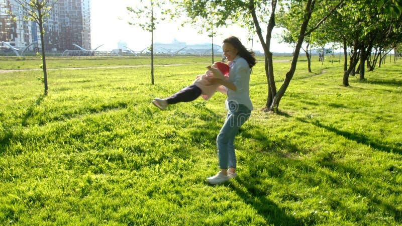 La jeune mère et son enfant entourent en parc Famille heureuse jouant sur le coucher du soleil images libres de droits