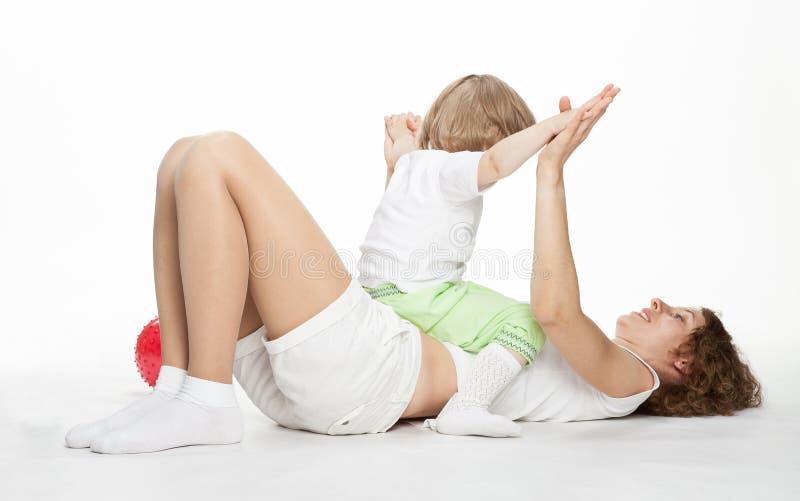 La jeune mère faisant le sport s'exerce avec la petite fille image libre de droits