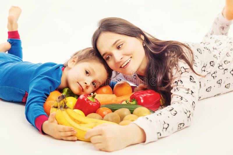 La jeune mère mange des fruits et légumes avec son jeune fils images stock