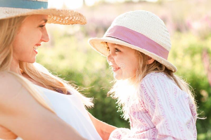 La jeune mère mignonne marche avec sa fille dans des ses bras image stock