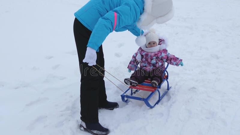 La jeune mère roule peu de bébé sur le traîneau le long de la route neigeuse en hiver L'enfant est vilain et des cris tout en se  image stock