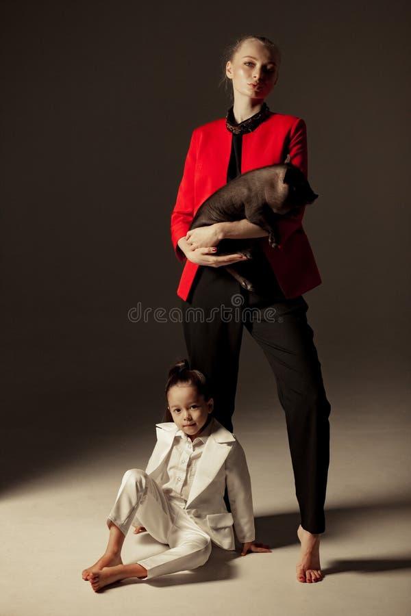 La jeune mère tient le porcelet vietnamien sur ses mains et poses avec photos stock