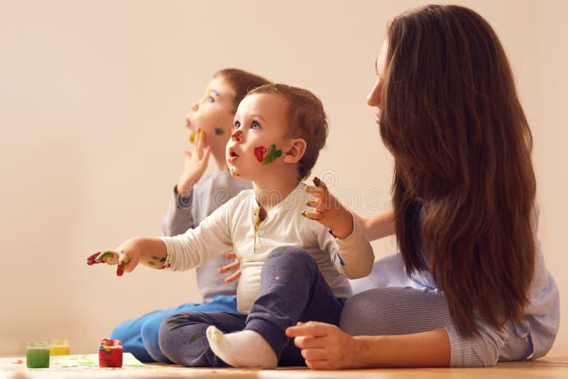 La jeune m?re et ses deux petits les fils habill?s dans des v?tements ? la maison s'asseyent sur le plancher en bois dans la cham image libre de droits