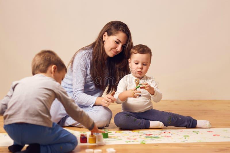 La jeune m?re heureuse et ses deux petits les fils habill?s dans des v?tements ? la maison s'asseyent sur le plancher en bois dan photos stock