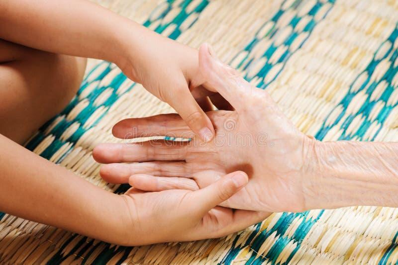 La jeune main touche et tient des mains de dame âgée image libre de droits