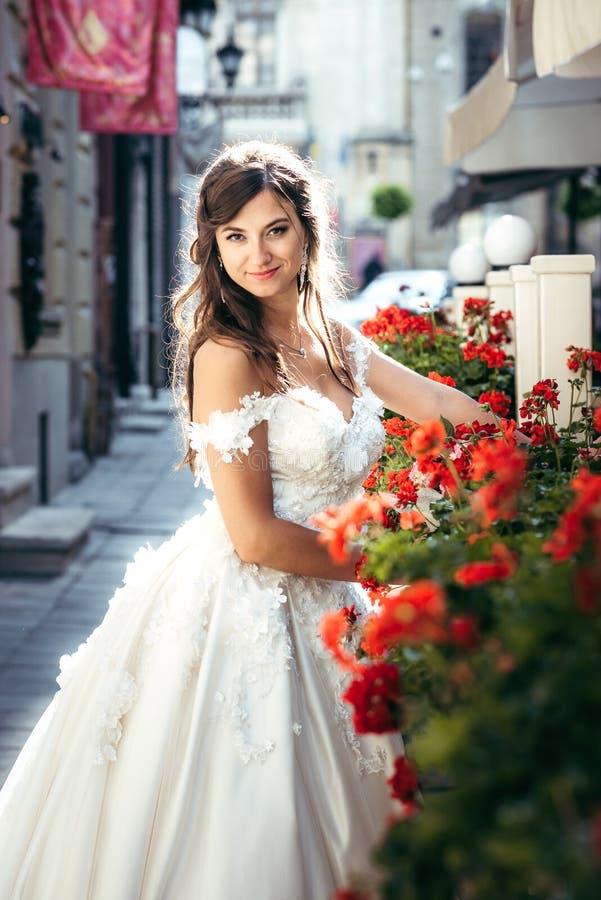 La jeune jeune mariée adorable de brune est souriante et posante dans la rue près des fleurs rouges images libres de droits