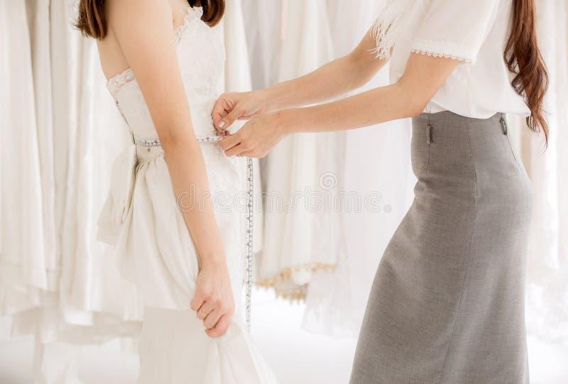 La jeune mariée asiatique de femme essayant sur la robe l'épousant, femmes travaillent faire l'ajustement avec la bande de mesure photographie stock
