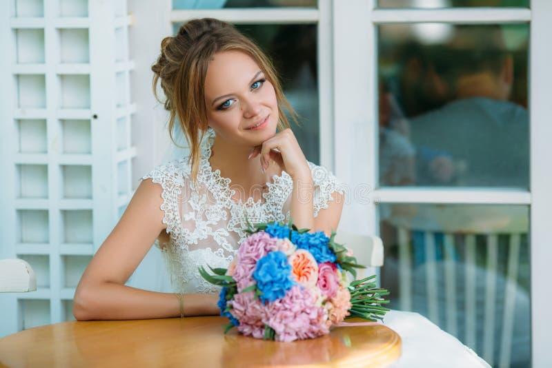 La jeune mariée blonde s'assied à une table et apprécie un beau jour Est tout près son bouquet rose-bleu de mariage Le bleu du `  image stock