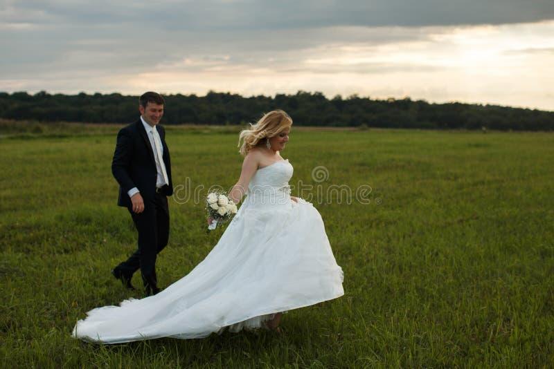 La jeune mariée court sur le champ vert tandis que le marié la suit photographie stock libre de droits