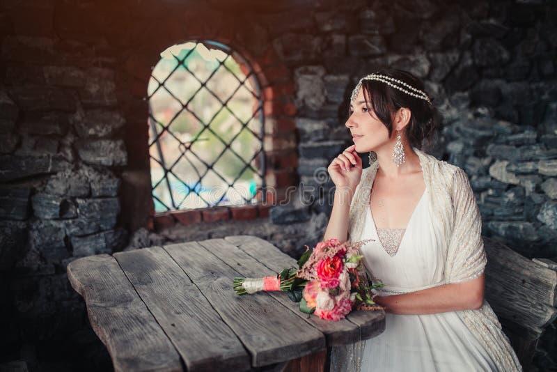 La jeune mariée dans le château à une table en bois image libre de droits