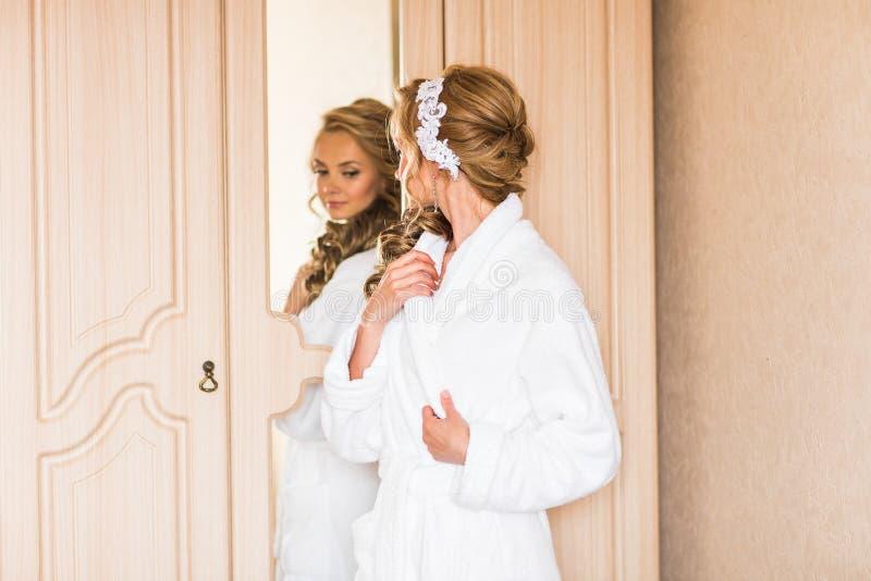 La jeune mariée dans le peignoir blanc Préparations de mariage image stock