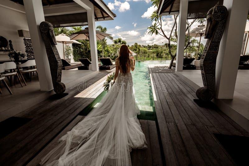 La jeune mariée dans la robe de mariage entre dans une piscine photographie stock