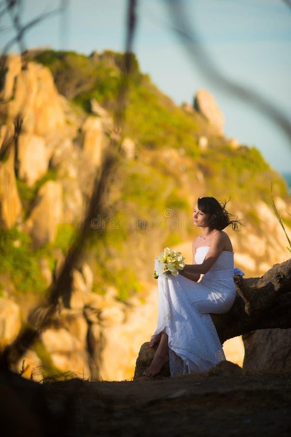 La jeune mariée dans la robe de mariage s'assied contre les montagnes asiatiques au coucher du soleil image libre de droits
