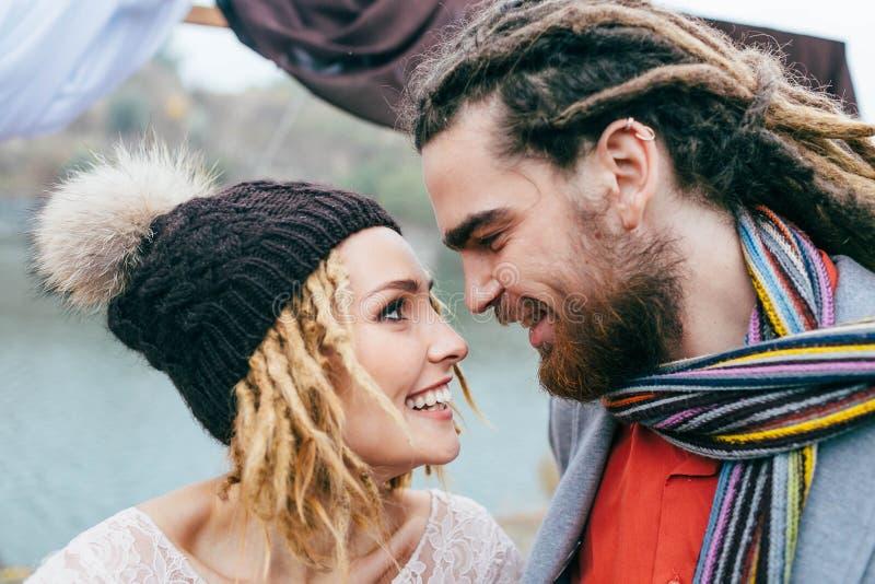La jeune mariée dans un chapeau tricoté avec le pompon et le marié avec des dreadlocks et l'écharpe regardent l'un l'autre avec l photo stock