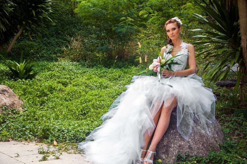 La jeune mariée dans un jardin photographie stock libre de droits