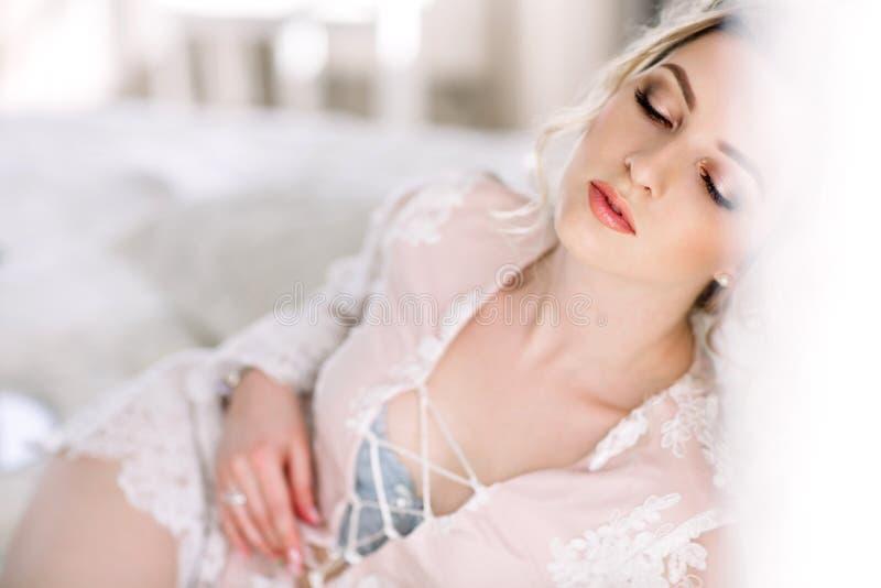 La jeune mariée dans un peignoir à la fenêtre de chambre à coucher pendant le matin image libre de droits
