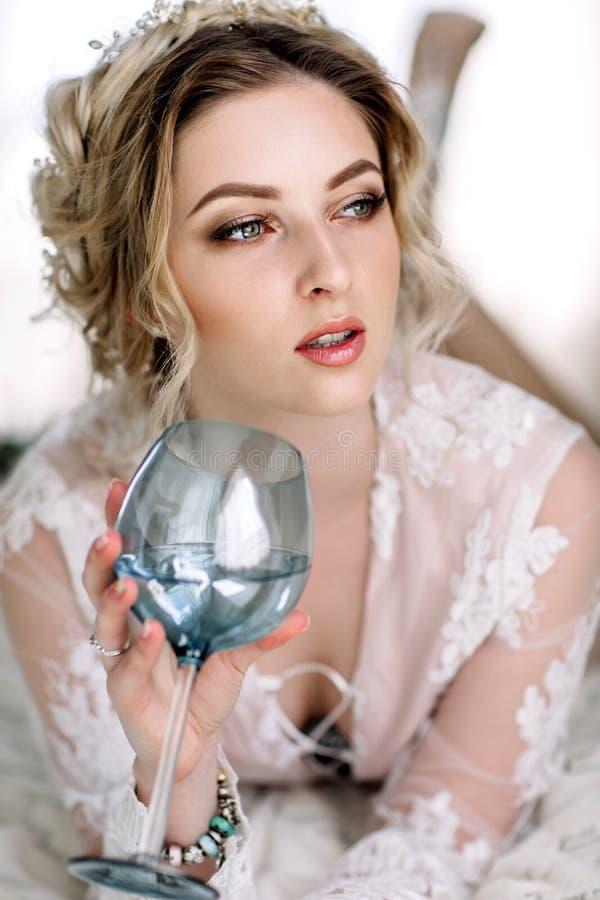 La jeune mariée dans un peignoir à la fenêtre de chambre à coucher pendant le matin photographie stock libre de droits