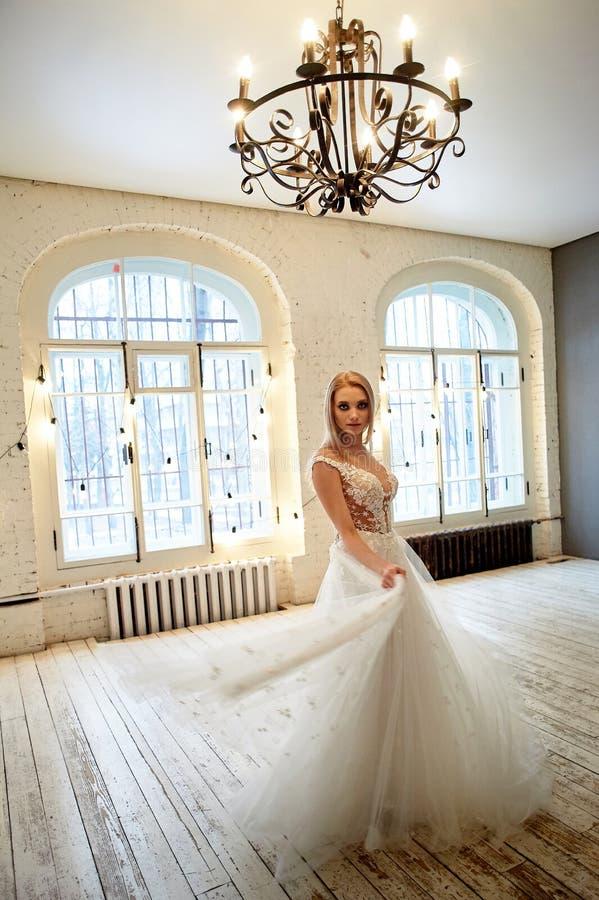 La jeune mari?e dans une robe blanche de dentelle avec le corsage brod? tourne dans la salle de style de grenier Cl? ?lev?e photographie stock libre de droits