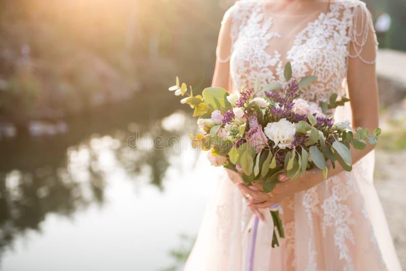 La jeune mariée dans une robe de mariage beige tenant un bouquet nuptiale luxuriant des roses lilas et de beaucoup de verdure Bou photographie stock