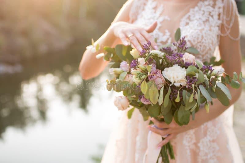 La jeune mariée dans une robe de mariage beige touchant un bouquet nuptiale luxuriant des roses lilas et de beaucoup de verdure B photos libres de droits