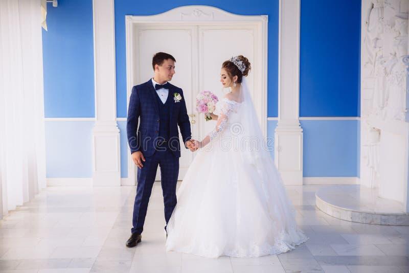 La jeune mariée dans une robe de mariage chic avec la broderie et un bouquet des pivoines dans sa main va à la grande porte blanc images stock