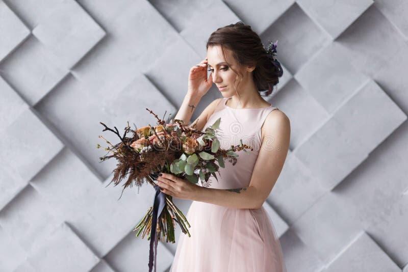 La jeune mariée de sourire avec le bouquet ferment le portrait dans le studio images libres de droits