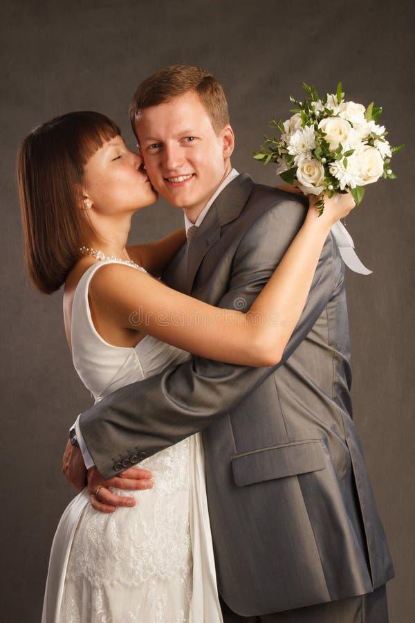 La jeune mariée embrasse le marié image stock