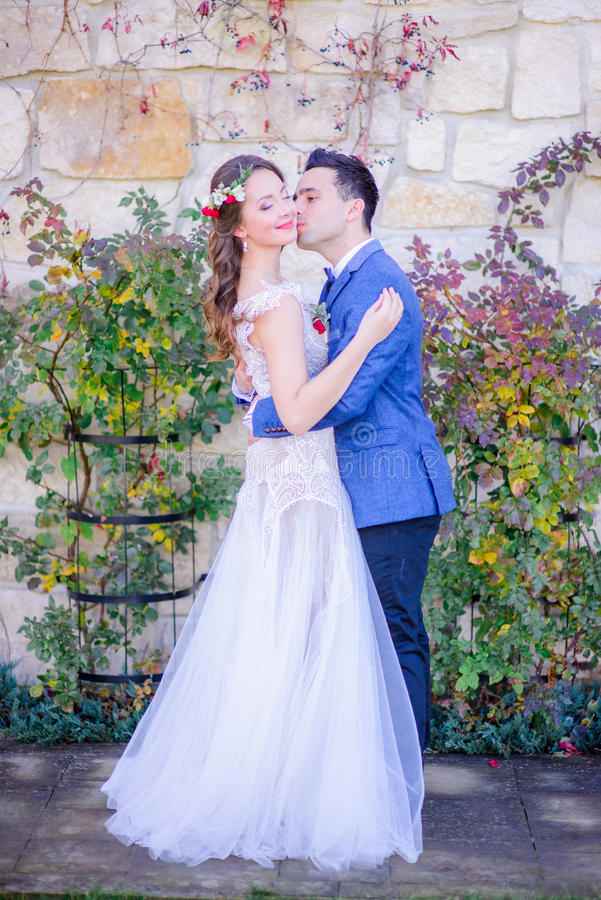 La jeune mariée en fleur rouge tressent des supports dans des étreintes du ` s de marié photographie stock