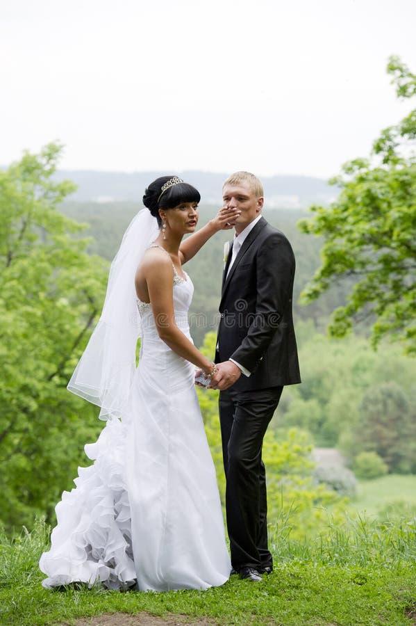 La jeune mariée essaye de faire taire le marié photos libres de droits